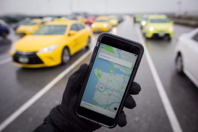 The Uber app is displayed on an iPhone as taxi drivers wait for passengers at Vancouver International Airport, in Richmond, B.C., on Tuesday, March 7, 2017.