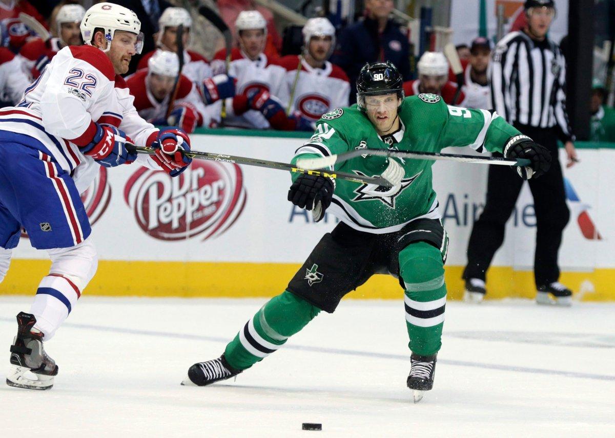 Dallas Stars center Jason Spezza and Montreal Canadiens defenseman Karl Alzner vie for control of the puck.
