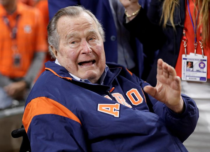 Former U.S. President George H.W. Bush waves from the field before Game 5 of the 2017 World Series between the Los Angeles Dodgers and the Houston Astros in Houston, Texas, on Oct. 29, 2017.