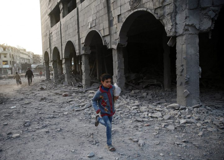 A Syrian boy runs past a damaged building in Douma, in the eastern Damascus suburb of Ghouta, Syria Nov. 15.