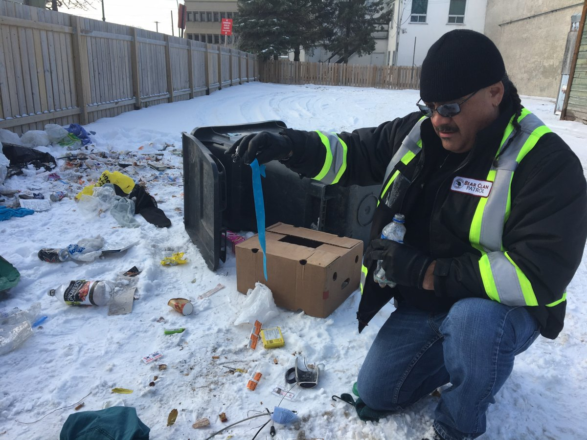 James Favel with the Bear Clan Patrol digs through garbage on the ground to remove needles.