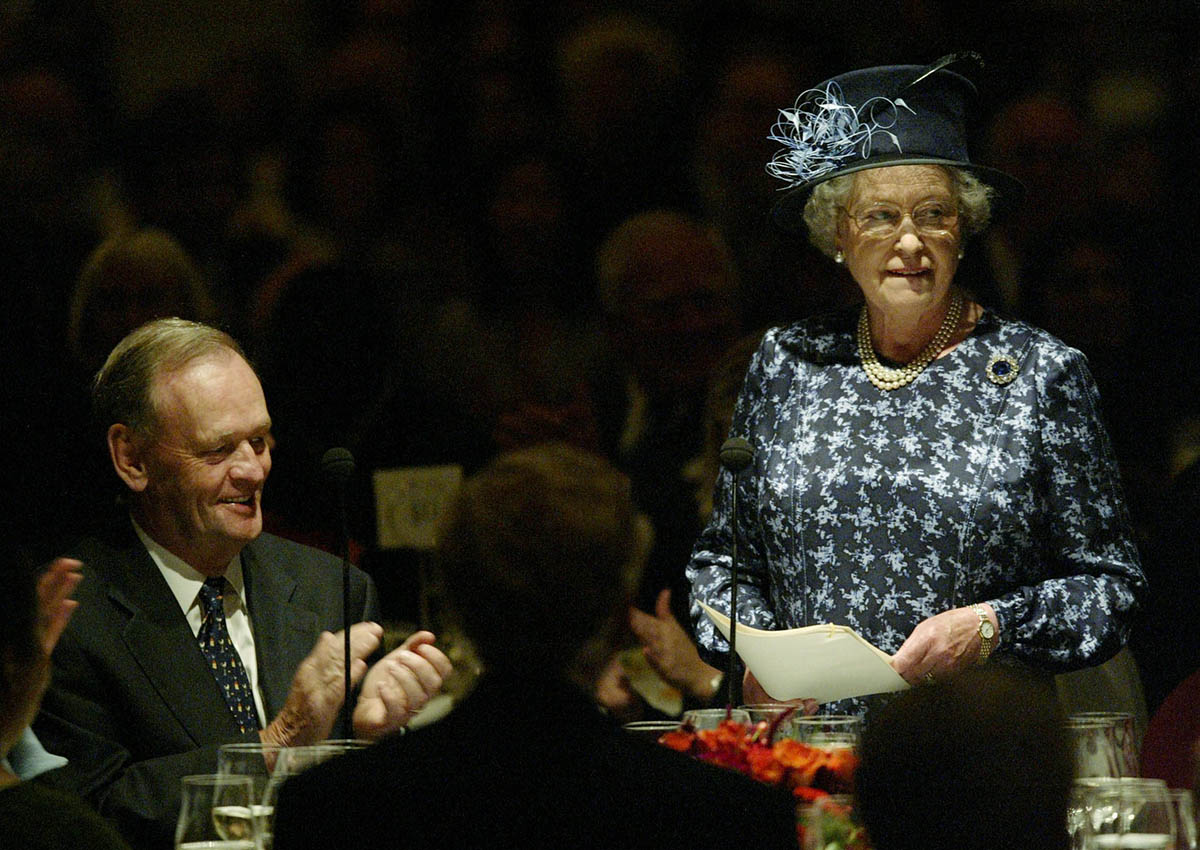 Canadian Prime Minister Jean Chretien listens to a speech by Queen Elizabeth during a luncheon in Vancouver October 7, 2002.