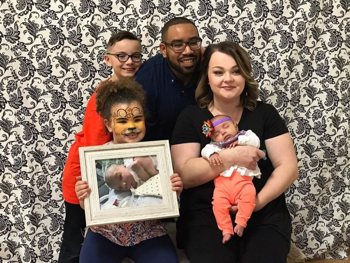 Brea Dean, bottom left, with brother Kaynen, father Dustin, mother Lisa and sister Maliyah, holds a photo of Aydrah.