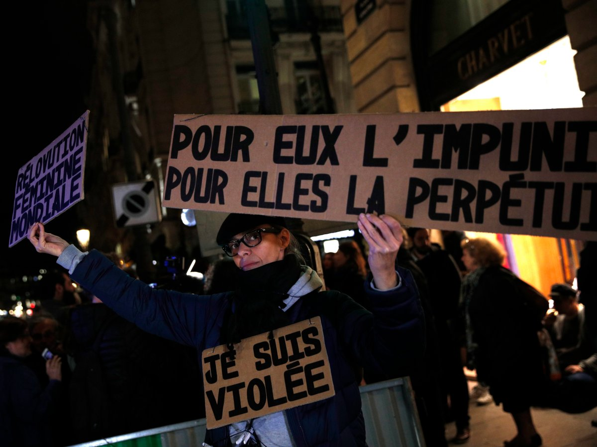 "A activist holds a banner reading: ""For him impunity, for her a life sentence"" during a protest in Paris, Nov. 14, 2017. Justice Minister Nicole Belloubet provoked consternation and dismay among feminist groups by saying a legal minimum age of 13 for sexual consent ""is worth considering."" ."