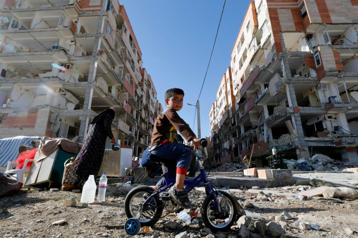 An Iranian boy rides a bicycle through the rubble caused by a 7.3-magnitude earthquake that left hundreds killed in November.