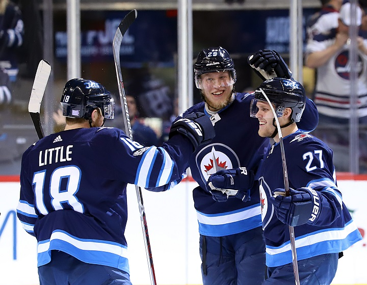 Bryan Little, Patrik Laine and Nikolaj Ehlers of the Winnipeg Jets celebrate a second period goal against the New Jersey Devils at Bell MTS Place on Nov 18 in Winnipeg.