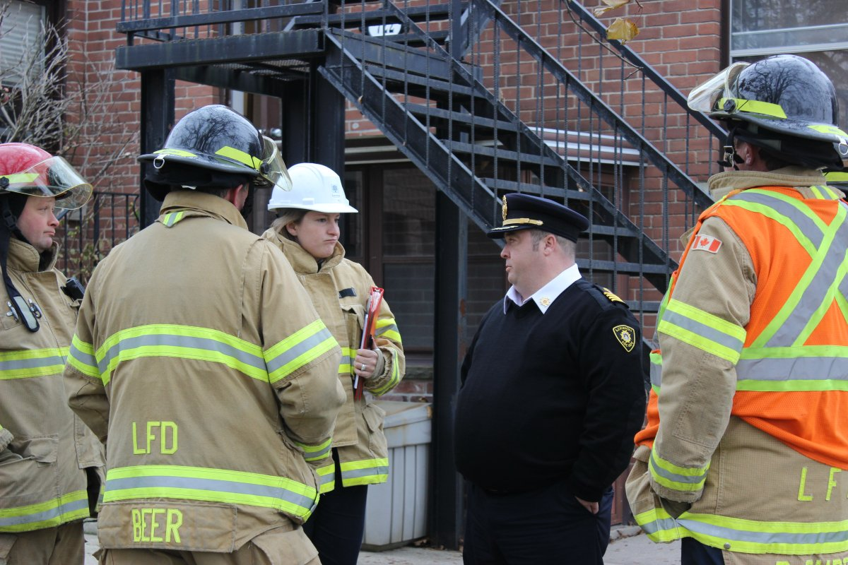 Assistant Deputy Fire Chief Jack Burt speaks with a group of firefighters outside of Maple Ridge, a 45-unit supportive housing facility, in November 2017.