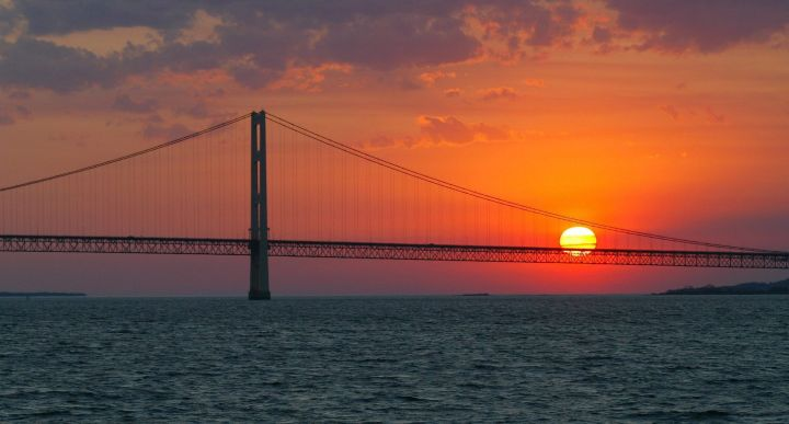 FILE - In this May 31, 2002 file photo, the sun sets over the Mackinac Bridge and the Mackinac Straits as seen from Lake Huron. The bridge is the dividing line between Lake Michigan to the west and Lake Huron to the east. Michigan's attorney general, Republican Bill Schuette, called Thursday, June 29, 2017 for shutting down the nearly 5-mile-long (8-kilometer-long) section of Enbridge Inc.'s Line 5 under the Straits of Mackinac.