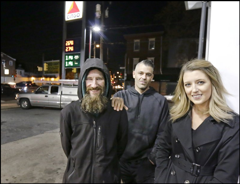 In this Nov. 17, 2017 photo, Johnny Bobbitt Jr., left, Kate McClure, right, and McClure's boyfriend Mark D'Amico pose at a CITGO station in Philadelphia. When McClure ran out of gas, Bobbitt, who is homeless, gave his last $20 to buy gas for her. McClure started a Gofundme.com campaign for Bobbitt that has raised more than $13,000.
