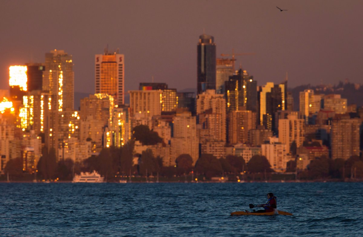 A woman paddles a kayak on the waters of English Bay as the sun reflects off windows on buildings in downtown Vancouver, B.C., at sunset on Sunday, September 27, 2015.