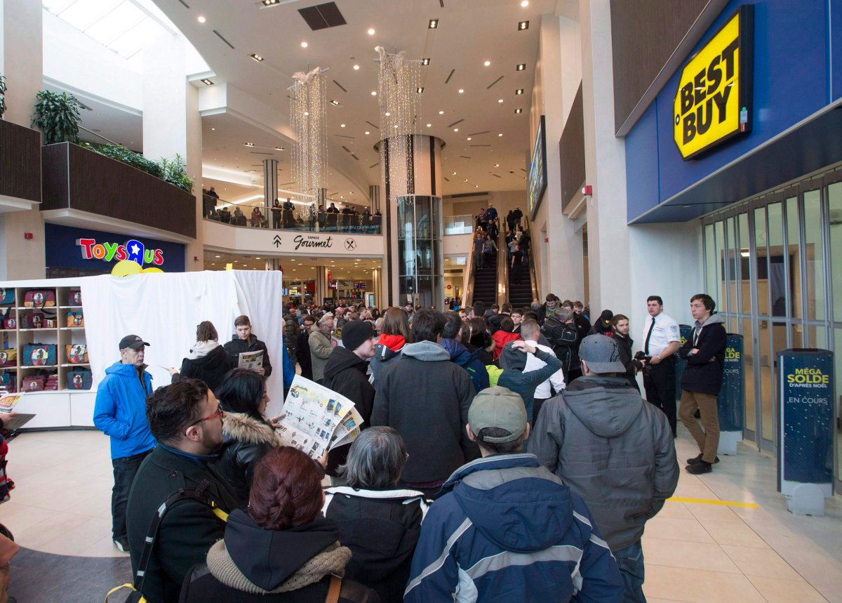Shoppers wait in line before the opening of a Best Buy in Quebec City on Boxing Day, Dec. 26, 2016.