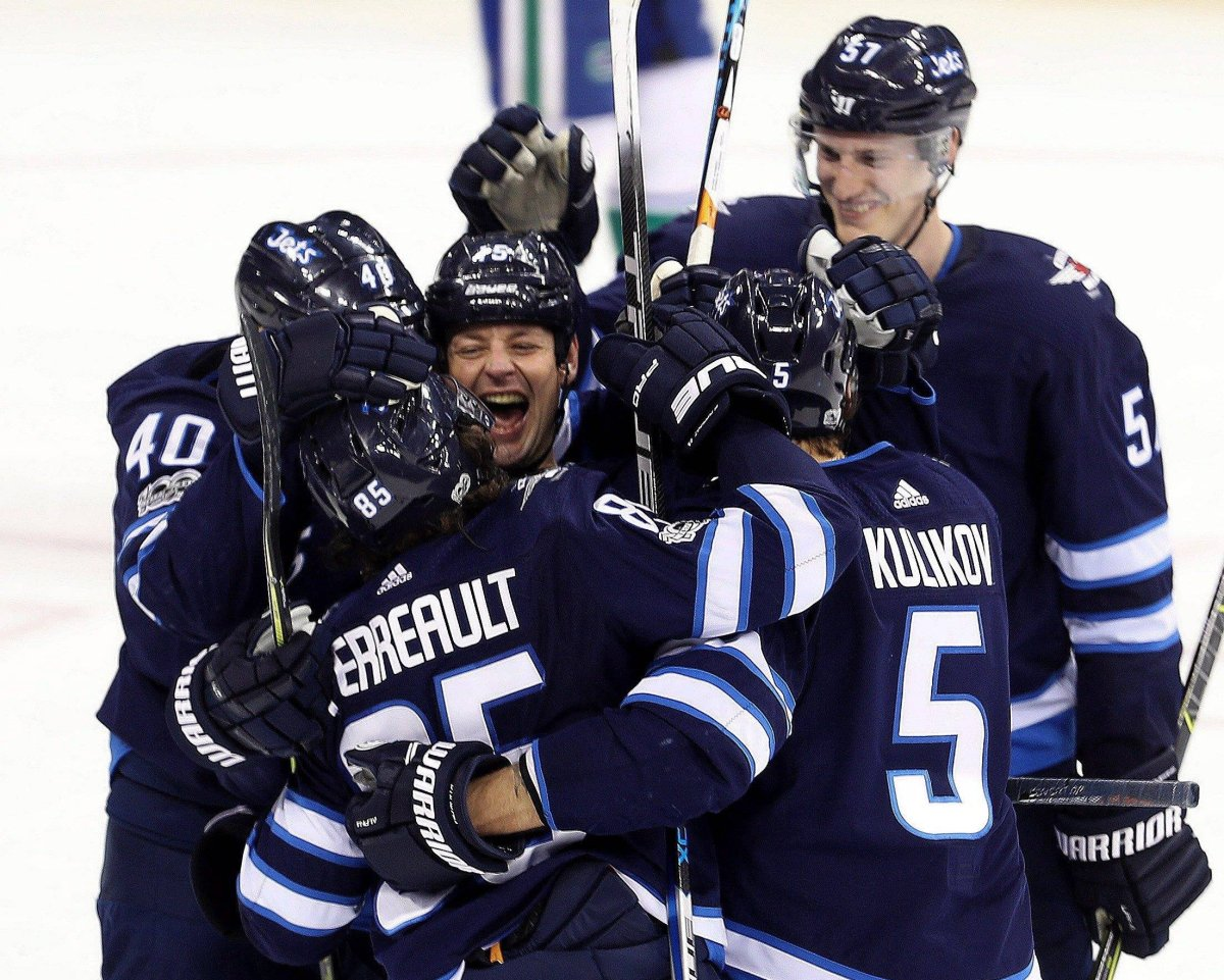 Winnipeg Jets' Matt Hendricks (15), middle, celebrates with Joel Armia (40), Mathieu Perreault (85), Dmitry Kulikov (5) and Tyler Myers (57) after Perreault's goal during third period NHL hockey action against the Vancouver Canucks, in Winnipeg, Monday, December 11, 2017. THE CANADIAN PRESS/Trevor Hagan.