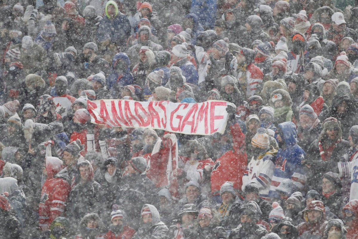 Hockey fans hold up a sign in the stands during the heavy snowfall at the IIHF World Junior Championship outdoor game between Canada and the U.S. at New Era Field in Orchard Park, N.Y., on Dec. 29, 2017.