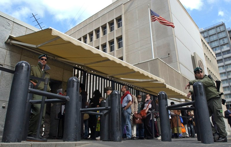 In this March 17, 2003, file photo, an Israeli border policemen guards the U.S. Embassy in Tel Aviv as other Israelis line up for U.S. visas. U.S. officials say U.S. President Donald Trump is poised to again delay his campaign promise to move the U.S. Embassy in Israel from Tel Aviv to Jerusalem.