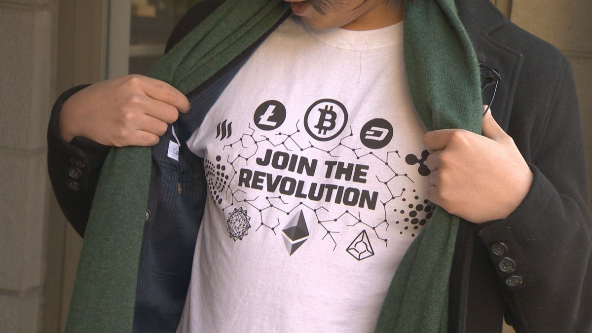 A man wears a T-shirt showing off several cryptocurrency logos.