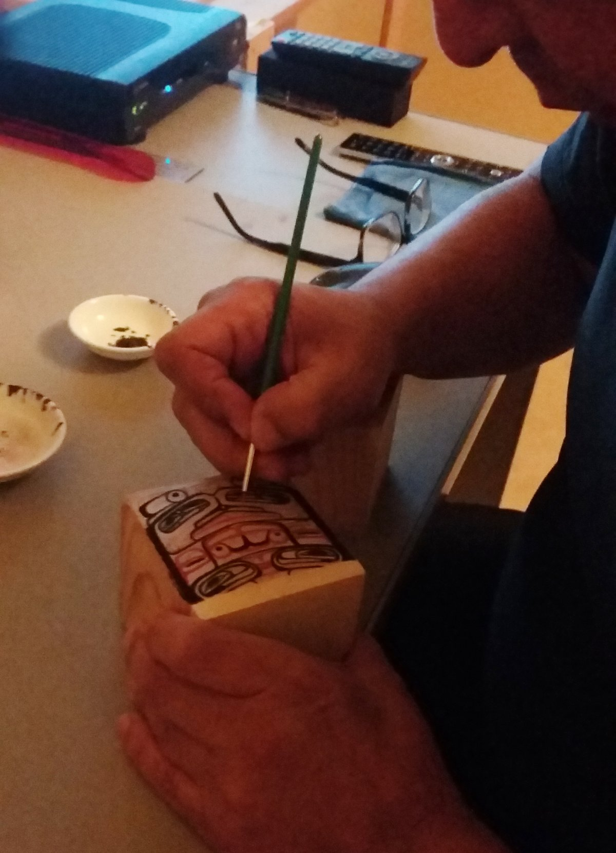 Andy Wilson of the Haida First Nation paints a delicate design on a traditional Haida bentwood box in this undated handout photo.