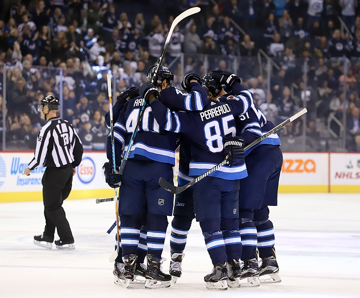 Joel Armia, Mathieu Perreault and Tyler Myers of the Winnipeg Jets celebrate a first period goal against the Vegas Golden Knights with teammates at Bell MTS Place on Dec. 1 in Winnipeg.