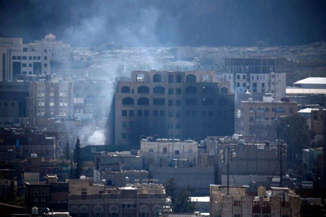 Smoke billows behind a building in the Yemeni capital Sanaa on Dec. 3, 2017, during clashes between Huthi rebels and supporters of Yemeni ex-president Ali Abdullah Saleh.