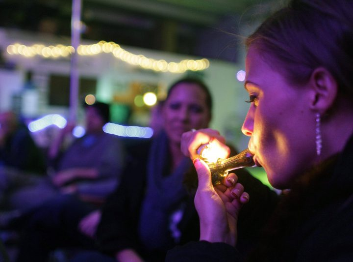 FILE - In this Dec. 31, 2012 file photo, a woman in Denver smokes marijuana on the official opening night of Club 64, a marijuana-specific social club, where a New Year's Eve party was held, in Denver.