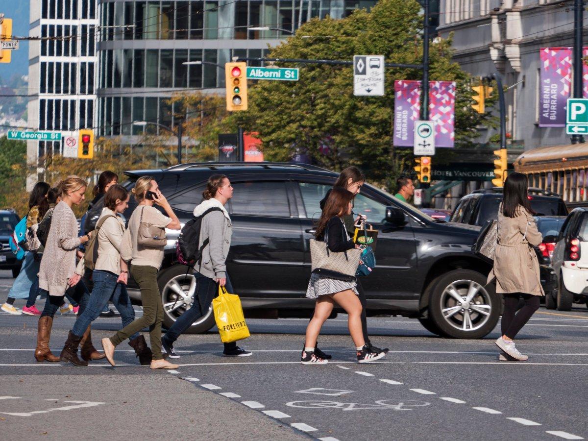 Pedestrians cross Burrard Street at Robson Street, downtown Vancouver, October 7, 2014.