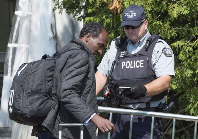 An asylum seeker shows his passport to an RCMP officer as crosses the border into Canada from the United States, Aug. 21, 2017 near Champlain, N.Y.