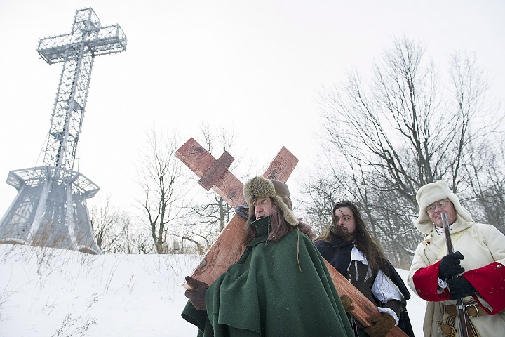 A man dressed as Paul de Chomedey de Maisonneuve, left, carries a crucifix to commemorate the 375th anniversary of the raising of the cross on Mount Royal in Montreal, Saturday, January 6, 2018.