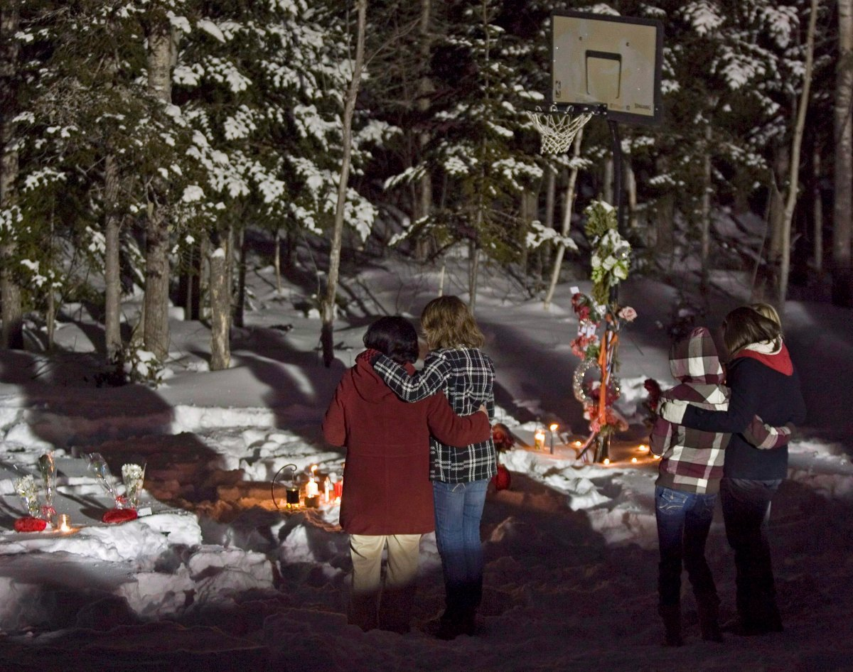 Family and friends pay their respects as they hold a vigil at the crash scene to mark the anniversary of the tragic accident that took the lives of seven high school basketball players and a teacher one year ago, in Bathurst, N.B. early on Monday, Jan. 12, 2009.