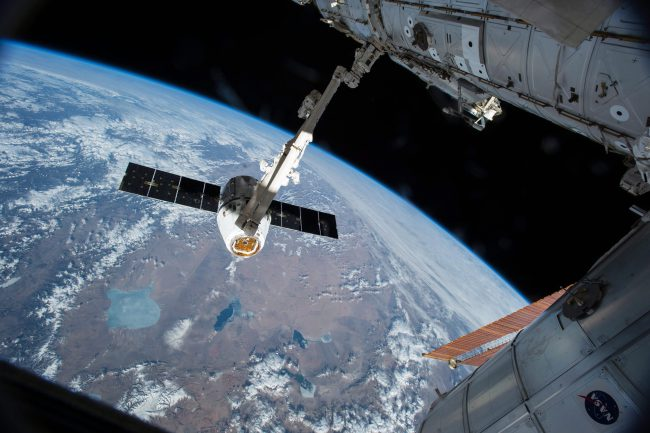 The Canadarm 2 reaches out to capture the SpaceX Dragon cargo spacecraft and prepare it to be pulled into its port on the International Space Station on April 17, 2015. T  .
