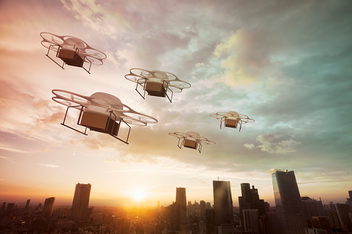 Five delivery drones flying above the city at sunset.