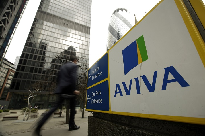 A pedestrian passes a sign outside the headquarters of Aviva Plc in London, U.K., on Friday, March 7, 2014.