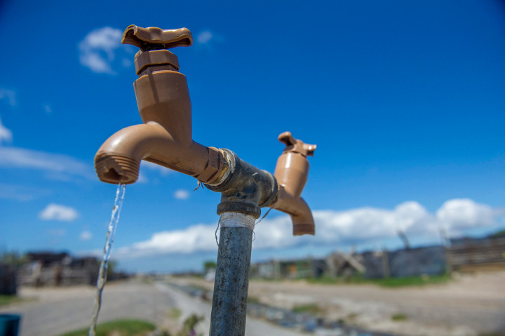 A communal tap runs as people collect water in an informal settlement near Cape Town, South Africa, Tuesday, Jan. 23, 2018.