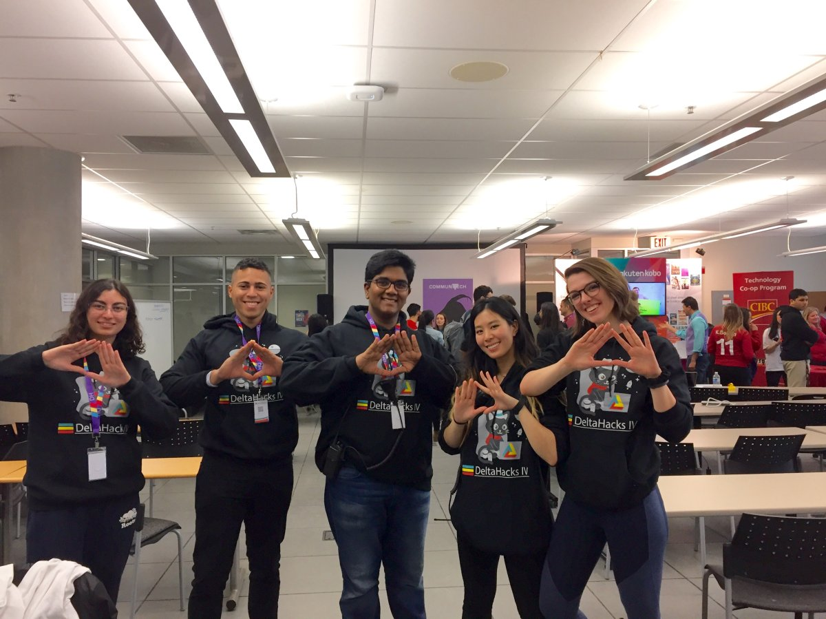 """Stephanie Koehl (right) and her fellow students make the """"Delta"""" hand symbol at McMaster University's fourth annual DeltaHacks hackathon."""