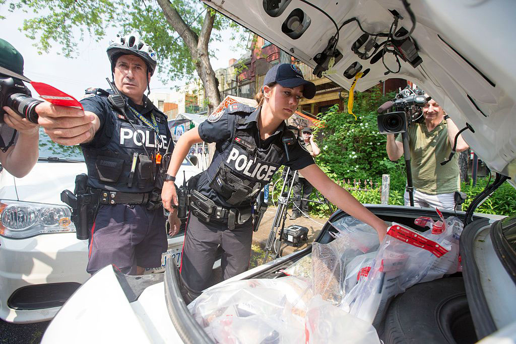 Police remove marijuana products from Cannawide dispensary in Toronto on May 26, 2016.