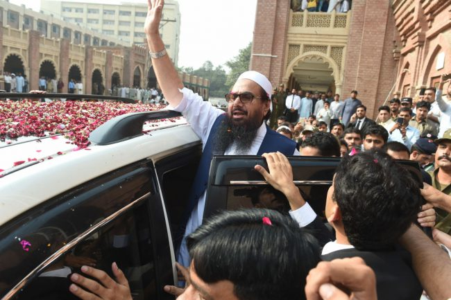 Pakistan head of the Jamaat-ud-Dawa (JuD) organisation Hafiz Saeed (C) waves to supporters as he leaves a court in Lahore on October 19, 2017.