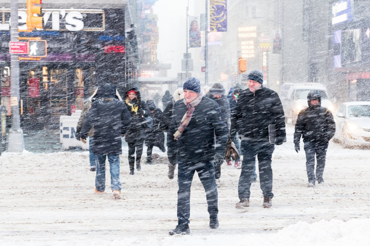 """TIMES SQUARE, NEW YORK, NY, UNITED STATES - 2018/01/04: People seen crossing the road during snow storm in Times Square. New York city is under heavy snow storm as a giant winter """"bomb cyclone"""" walloped the East Coast of United States with freezing cold air and heavy snow."""