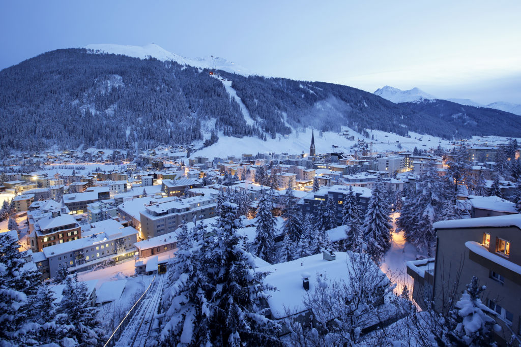 St. John's church, centre right, sits surrounded by snow-covered residential buildings as night falls in Davos, Switzerland, on Monday, Jan. 18, 2015.
