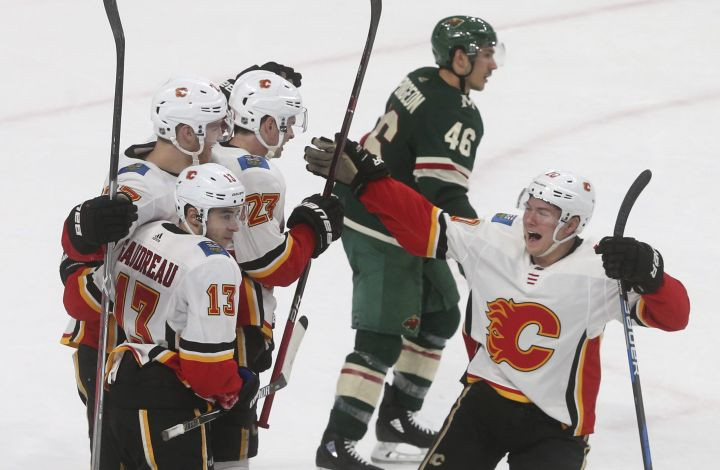 Minnesota Wild's Jared Spurgeon, top center, skates away as Calgary Flames' Dougie Hamilton (27) is congratulated on his winning goal in overtime of an NHL hockey game Tuesday, Jan. 9, 2018, in St. Paul, Minn. The Flames won 3-2. Spurgeon scored the game-tying goal in the third period for the Wild.
