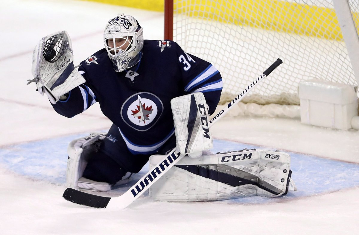 Winnipeg Jets' goaltender Michael Hutchinson (34) makes a glove save against the Tampa Bay Lightning during third period NHL hockey action in Winnipeg, Tuesday, Jan. 30, 2018.