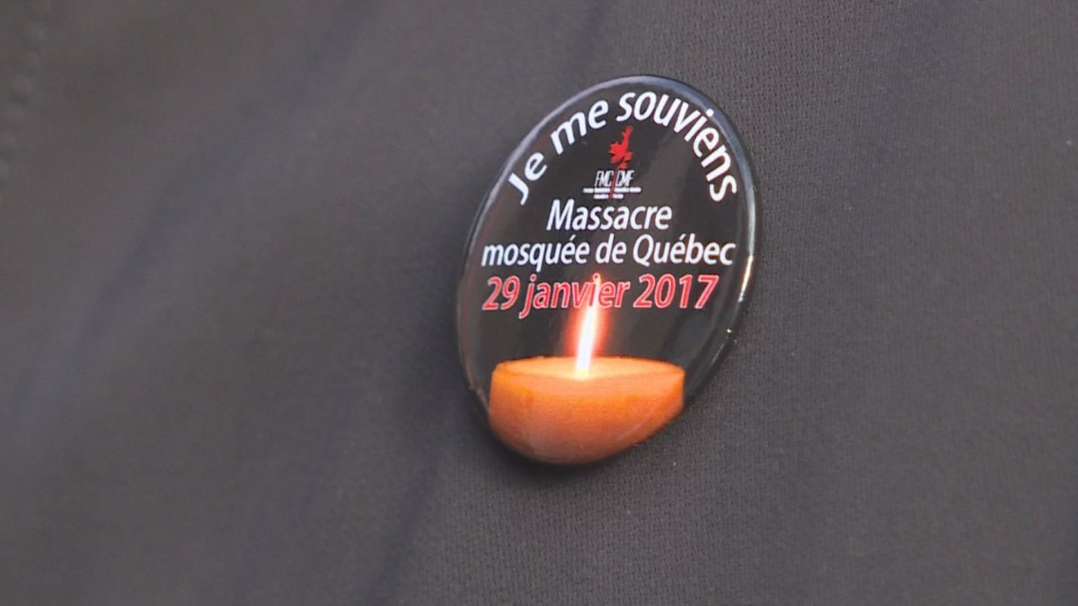 A woman wears a pin commemorating the first anniversary of the Quebec City mosque shooting, during an event in Montreal, Sunday, Jan. 28, 2018.