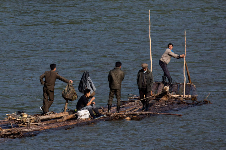 In this Aug. 30, 2017 photo, North Korean men ride a makeshift raft made of fastened logs down the Yalu river that divides North Korea from the Chinese border town of Linjiang in northeastern China's Jilin province.