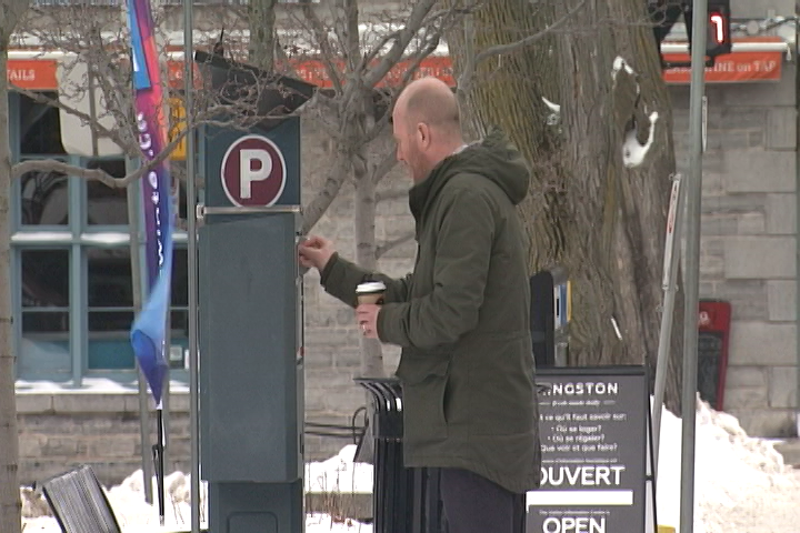 A man feeds an on-street parking meter on Ontario Street in Kingston, Ontario.