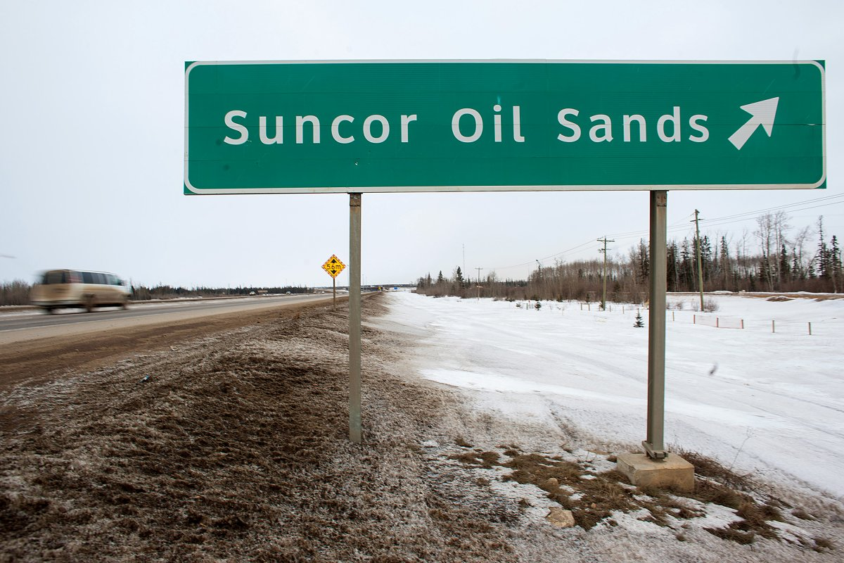 FILE: A sign directing traffic to the Suncor Energy Inc. base plant stands at the Athabasca Oil Sands near Fort McMurray, Alberta, Canada, on Tuesday, March 26, 2013.