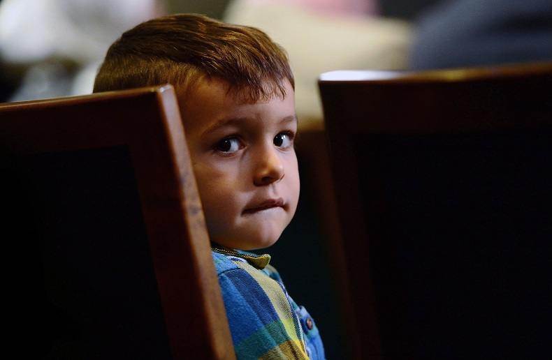 Sebastian Khan, 3, of London, Ontario sits patiently as his mother talks about his name being on the Canada's No Fly List during a press conference on Parliament Hill in Ottawa last November.