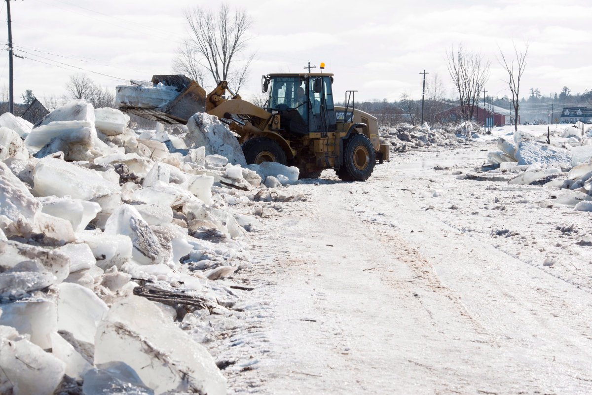 Tim McCann uses a front end loader to remove ice off of Route 101 in Hoyt, N.B., on Sunday, Jan. 14, 2018.