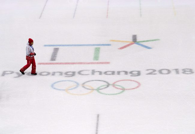 A worker walks across the Pyeongchang 2018 logo in the figure skating venue during the XXIII Olympic Winter Games in Gangneung, South Korea on Thursday, February 8, 2018.