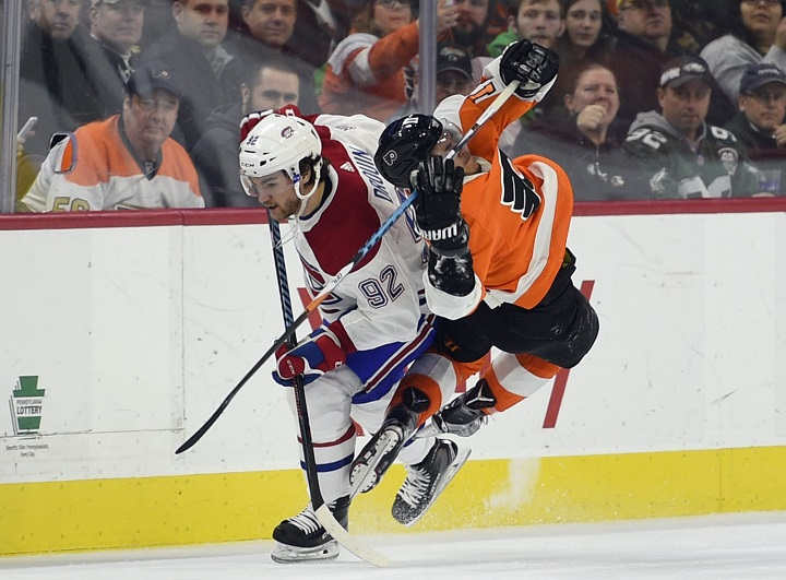 Philadelphia Flyers' Travis Konecny, right, is tripped by Montreal Canadiens' Jonathan Drouin (92) during the third period of an NHL hockey game Thursday, Feb. 8, 2018, in Philadelphia. The Flyers won 5-3.