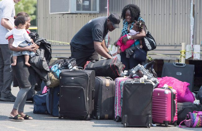 Asylum seekers sort out their luggage at a processing centre after crossing the border into Canada from the United States, August 21, 2017 near Saint-Bernard-de-Lacolle, Que.