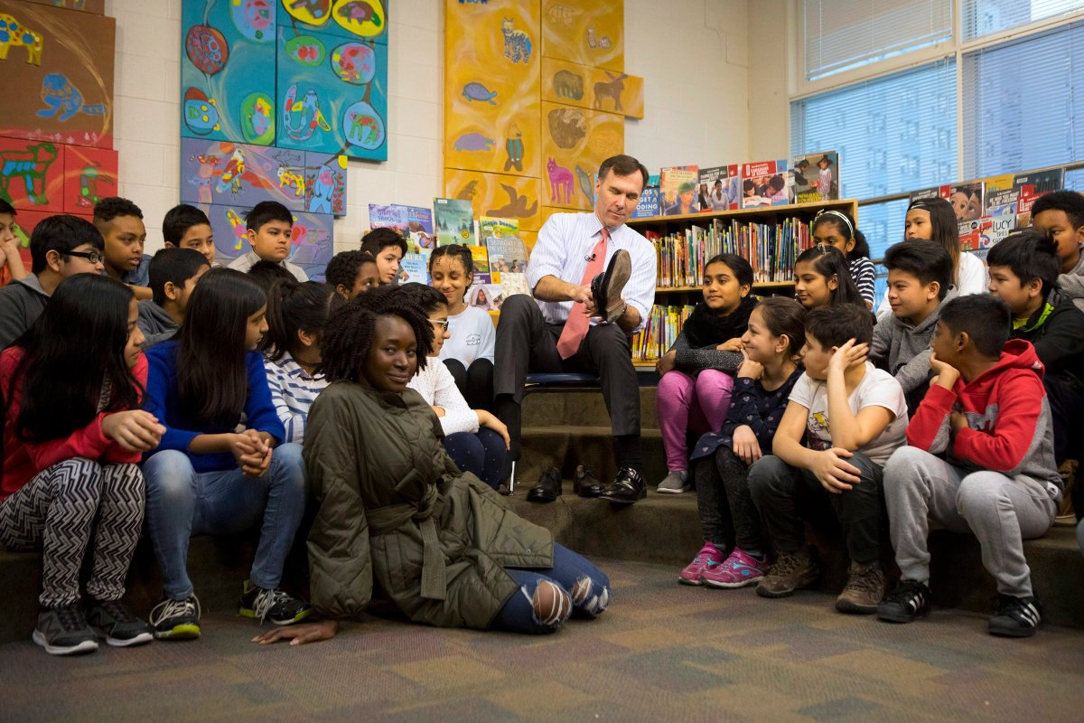 Federal Finance Minister Bill Morneau is joined by students from Toronto's Rose Avenue Junior Public School and his adopted daughter Grace as he tries on a pair of shoes from Edmonton's Poppy Barley Shoe manufacturer during a pre-budget photo opportunity in Toronto on Friday February 23, 2018.