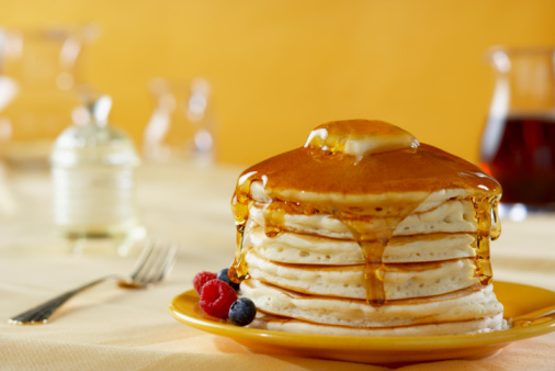 Pancakes with maple syrup on a set table.