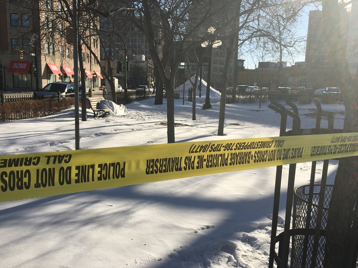 Police tape surrounds a downtown Winnipeg park after a body was found on a bench Thursday.